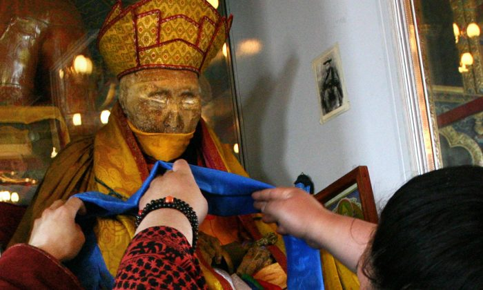 An undated photo shows a believer decorating the mummy of Dasha-Dorjo Itighelov, a Siberian Buddhist leader who looks and feels just the same as when he died in 1927 in a temple in Ulan-Ude, the capital of the Buryat republic.  (HO/AFP/Getty Images)