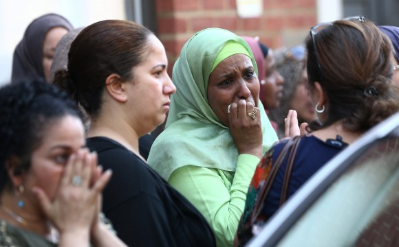 People react near a tower block severely damaged by a serious fire, in north Kensington, West London, Britain June 14, 2017. REUTERS/Neil Hall