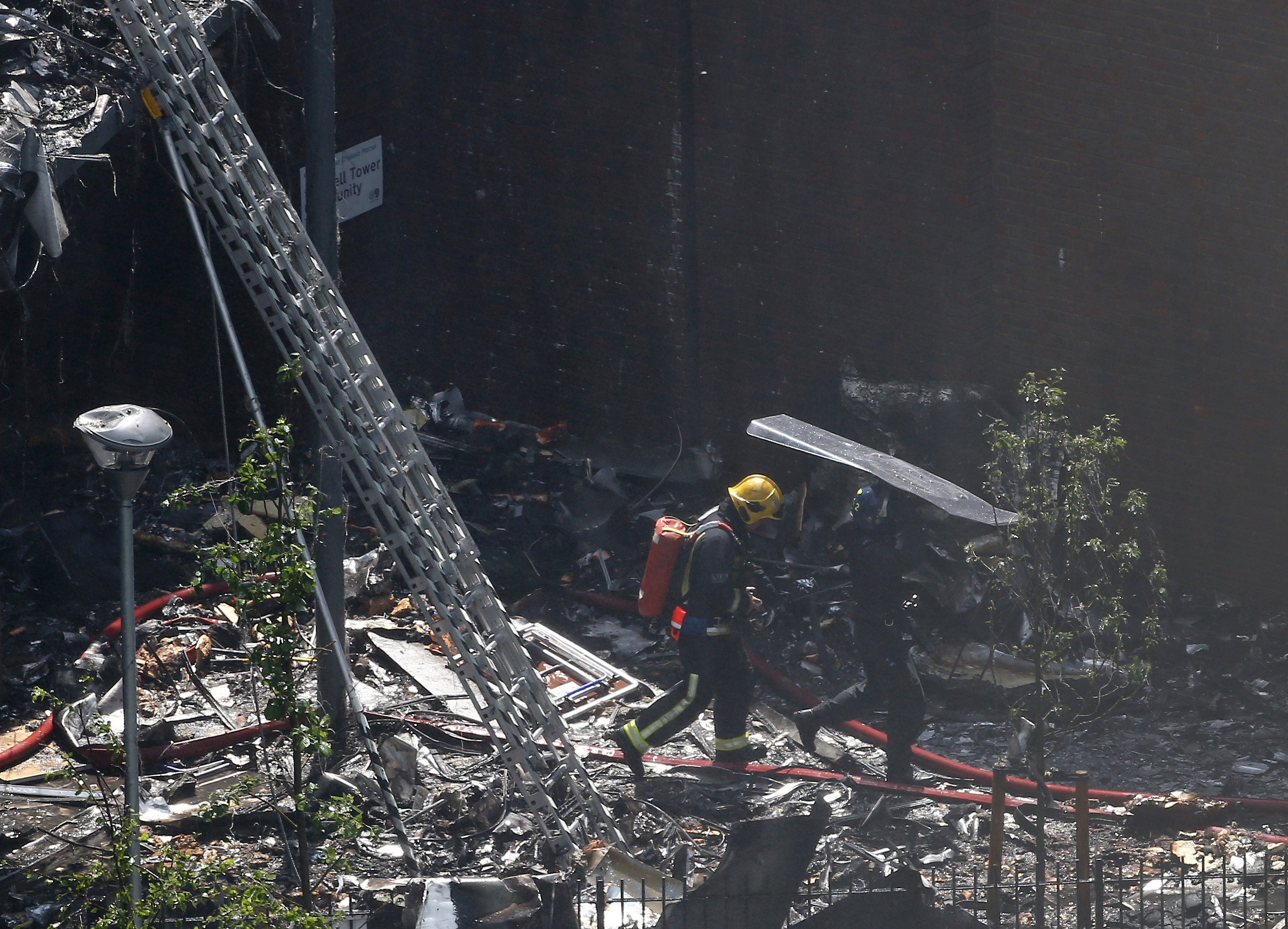 A police officer holds a riot shield over a firefighter at a tower block severely damaged by a fire in West London, Britain on June 14, 2017. (REUTERS/Neil Hall)
