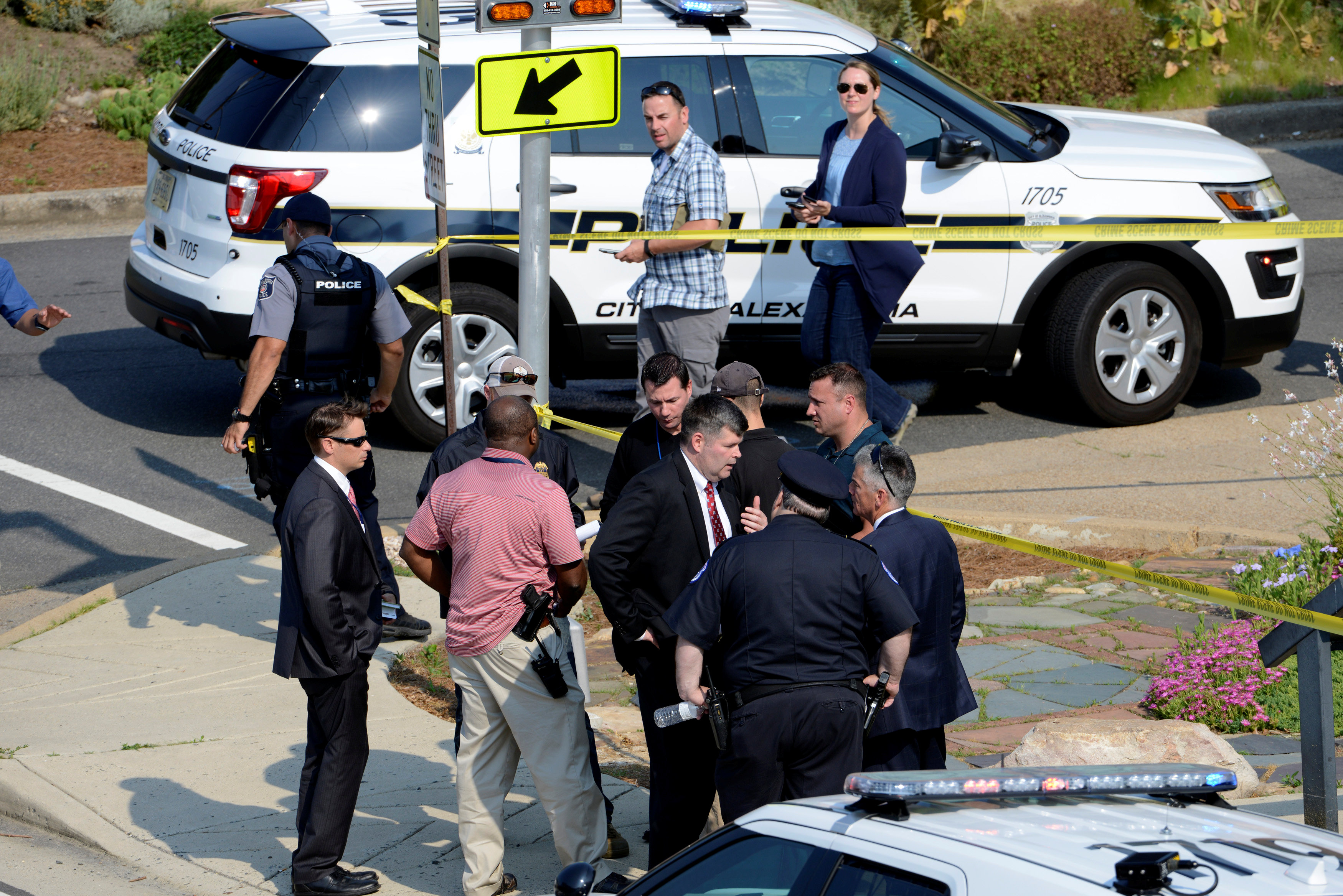 Police and investigators gather at an intersection near the scene where shots were fired during a congressional baseball practice, wounding House Majority Whip Steve Scalise (R-LA), in Alexandria, Virginia on June 14, 2017. (REUTERS/Mike Theiler)