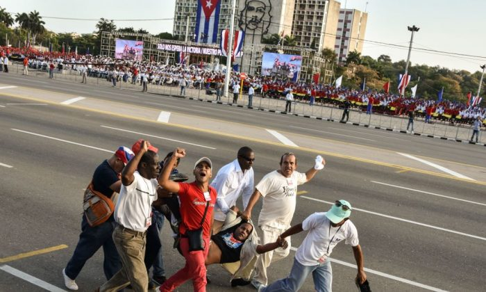 A man who burst in of the May Day march waving a US flag is taken away, at Revolution Square in Havana, on May 1, 2017. (ADALBERTO ROQUE/AFP/Getty Images)