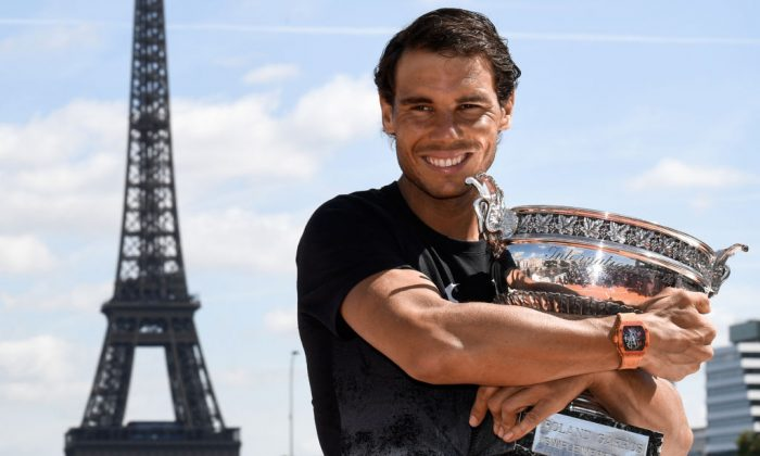 Spain's Rafael Nadal shows off the winner's trophy on June 12, 2017, a day after he won the men's Roland Garros 2017 French Open, in Paris, with the Eiffel Tower in Background. (Christophe Simon/AFP/Getty Images)