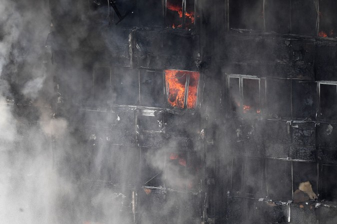 LONDON, ENGLAND - JUNE 14: Flames continue to burn after a huge fire engulfed the 24 storey residential Grenfell Tower block in Latimer Road, West London in the early hours of this morning on June 14, 2017 in London, England. The Mayor of London, Sadiq Khan, has declared the fire a major incident as more than 200 firefighters are still tackling the blaze while at least 50 people are receiving hospital treatment. (Photo by Leon Neal/Getty Images)