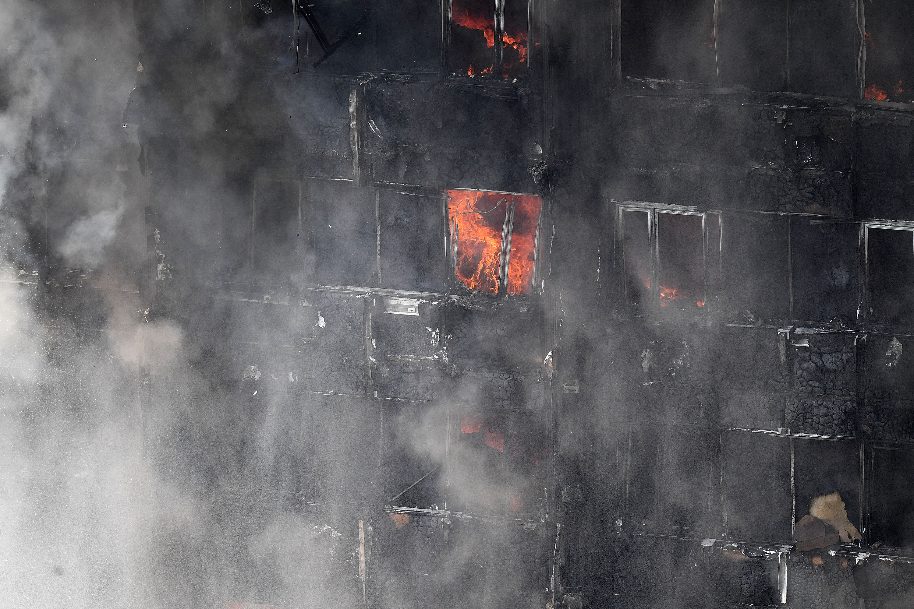 Flames continue to burn after a huge fire engulfed a 24-story residential Grenfell Tower block in West London in the early hours of June 14, 2017.  (Photo by Leon Neal/Getty Images)