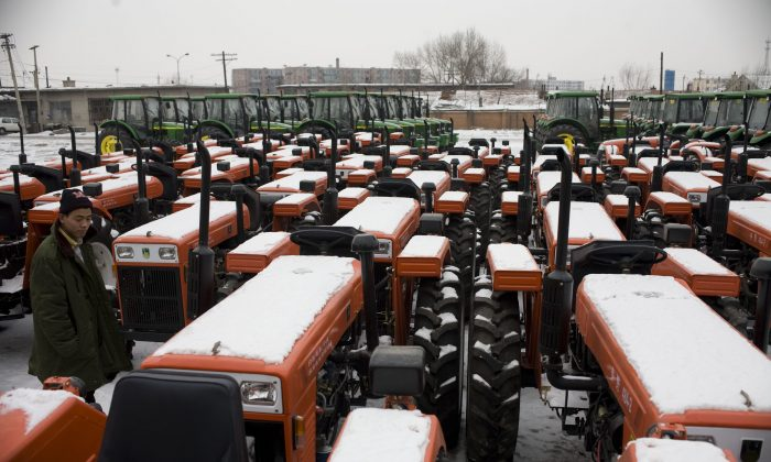 A farmer looks at tractors at a farm machine factory on February 21, 2009 in Changchun, Jilin Province, China. (China Photos/Getty Images)
