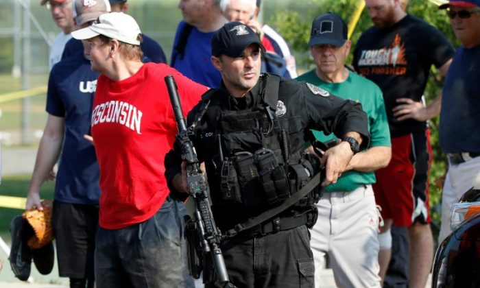 A U.S. Capitol police SWAT team officer escorts members of Congress and congressional staff from the scene after a gunman opened fire on Republican members of Congress during a baseball practice near Washington in Alexandria, Virginia, on  June 14, 2017. (Joshua Roberts/REUTERS)