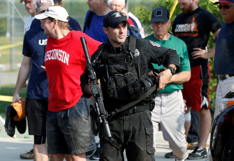 A U.S. Capitol police SWAT team officer escorts members of Congress and congressional staff from the scene after a gunman opened fire on Republican members of Congress during a baseball practice near Washington in Alexandria, Virginia on  June 14, 2017. (REUTERS/Joshua Roberts)