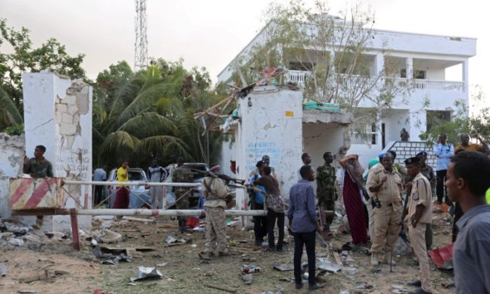 People stands outside the scene of an attack on a hotel and an adjacent restaurant in Mogadishu, Somalia June 15, 2017. (Reuters/Stringer)