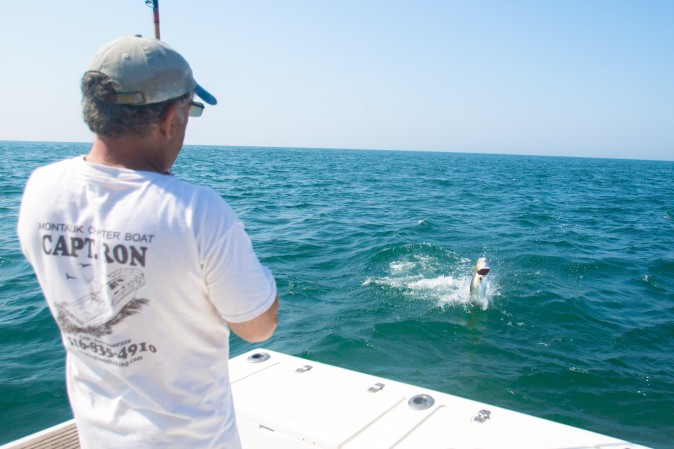 Fisherman Ron Onorato catches a bluefish in the waters off the Montauk shore in Long Island, New York, using traditional rod-and-reel methods. (Benjamin Chasteen/The Epoch Times)