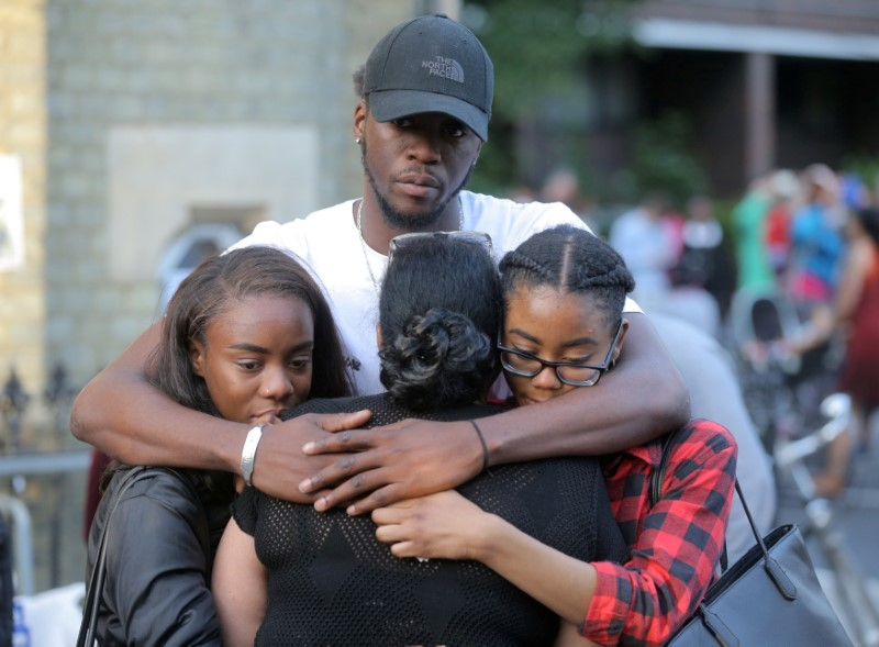 People comfort each other after a prayer vigil outside Notting Hill Methodist Church close to the tower block severely damaged by a serious fire, in north Kensington, West London. (REUTERS/Paul Hackett)
