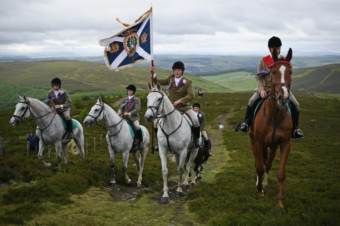 Standard bearer Kieran Riddell and his attendants arrive at The Three Brethren as they take part in the Common Riding, one of the oldest Borders festivals in Selkirk, Scotland, on June 16, 2017. The event dating from the Battle of Flodden in 1513, remembers the story when the town of Selkirk sent 80 men into battle with the Scottish king. One man returned, bearing a blood-stained English flag. (Jeff J. Mitchell/Getty Images)