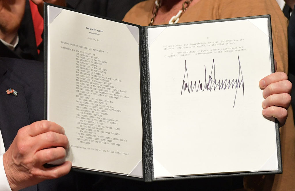 US President Donald Trump holds up a memorandum he signed on the US/ Cuba policy after he spoke at the Manuel Artime Theater in Miami, Fla., on June 16, 2017. (MANDEL NGAN/AFP/Getty Images)
