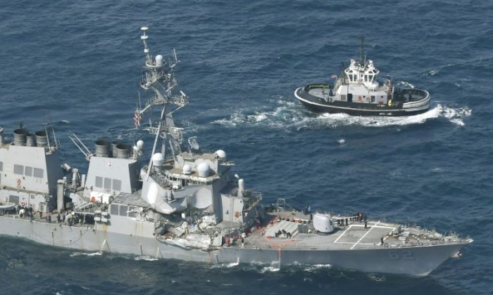 The Arleigh Burke-class guided-missile destroyer USS Fitzgerald, damaged by colliding with a Philippine-flagged merchant vessel, is seen next to a tugboat (R) off Shimoda, Japan in this photo taken by Kyodo June 17, 2017. Mandatory credit Kyodo/via REUTERS
