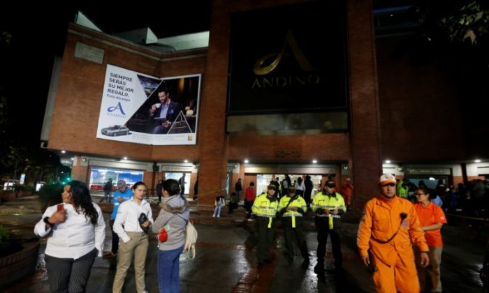 People, police officers and rescue personnel stand outside the Andino shopping center after an explosive device detonated in a restroom, in Bogota, Colombia June 17, 2017. (Reuters/Jaime Saldarriaga)