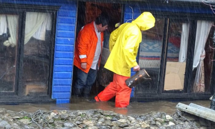 Residents of a house are seen on a flooded street due to torrential rains causing a river to overflow, in Curanilahue city, south of Chile,  June 16, 2017. (Reuters/Manuel Araneda)