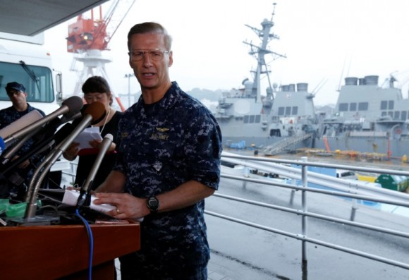 Vice Admiral Joseph Aucoin, U.S. 7th Fleet Commander, speaks to media on the status of the U.S. Navy destroyer USS Fitzgerald (seen behind him), damaged by colliding with a Philippine-flagged merchant vessel, and the seven missing Fitzgerald crew members, at the U.S. naval base in Yokosuka, south of Tokyo, Japan June 18, 2017. (Reuters/Toru Hanai)