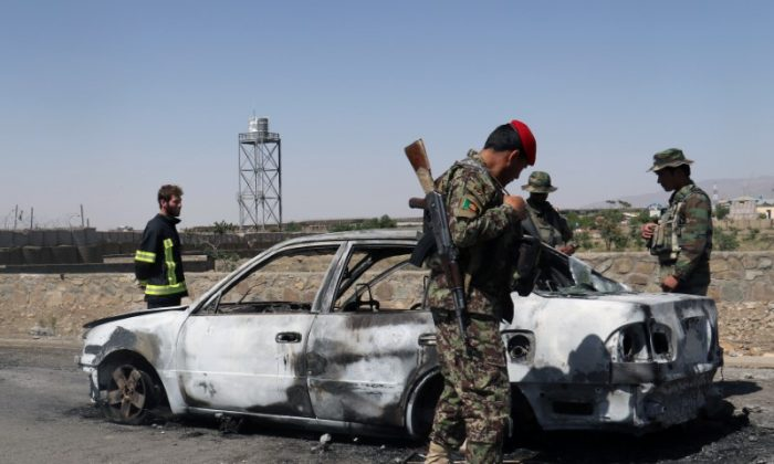Afghan security forces inspect the exterior of a car after a suicide bomb blast in Paktia Province, Afghanistan June 18, 2017. (Reuters/Samiullah Peiwand)