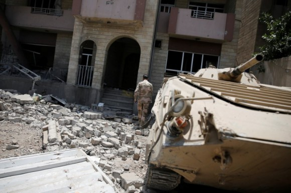 A member of the Iraqi Army's 9th Armoured Division walks among debris at the yard of a destroyed building at the frontline in western Mosul, Iraq June 17, 2017. REUTERS/Alkis Konstantinidis
