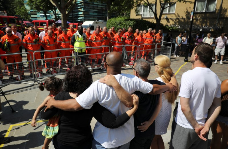 Members of the emergency services join people in a minute's silence for the victims of the Grenfell Tower fire near the site of the blaze in North Kensington, London, Britain, June 19, 2017. REUTERS/Marko Djurica