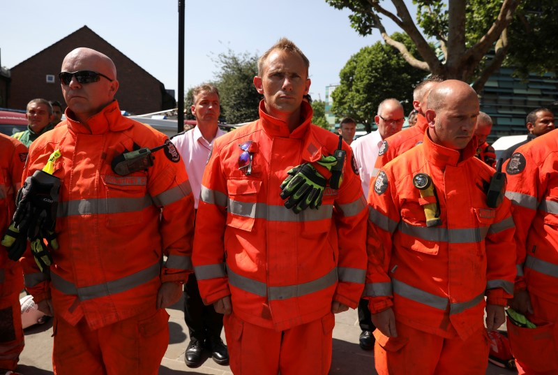 Members of the emergency services attend a minute's silence for the victims of the Grenfell Tower fire near the site of the blaze in North Kensington, London, Britain on June 19, 2017. (REUTERS/Marko Djurica)