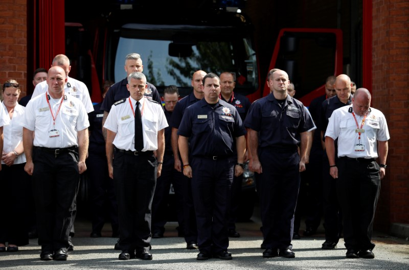 Firefighters from the Manchester Central Community Fire Station observe a minute's silence in memory of the victims of the fire that destroyed London's Grenfell Tower block, in Manchester on June 19, 2017. (REUTERS/Phil Noble)