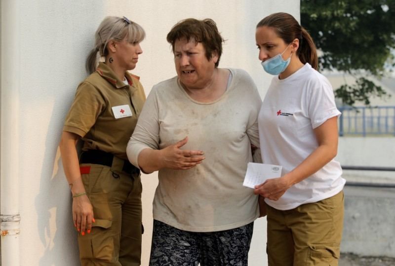 A woman is attended by Red Cross workers outside a relief center for people affected by a forest fire in Figueiro dos Vinhos, Portugal on June 19, 2017. (REUTERS/Miguel Vidal)
