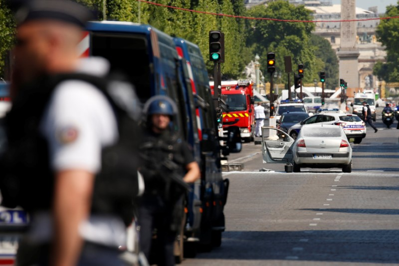 French policemen secure the area around a burned car on the Champs Elysees avenue after an incident in Paris, France, June 19, 2017. REUTERS/Gonzalo Fuentes