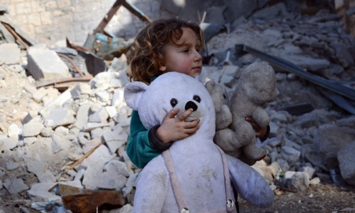A Syrian girl, holding her stuffed toy, stands next to the rubble of buildings in the northwestern Syrian border town of al-Bab on February 25, 2017 (Nazeer Al-Khatib/AFP/Getty Images)