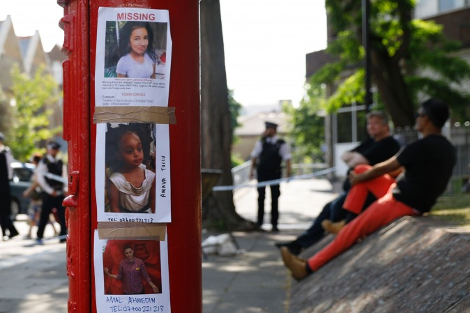 The pictures of people missing after the Grenfell Tower block fire, (top-bottom) Jessica Urbano, Amava Tuccu and Amal Ahmedin, are seen taped to a post box near the scene in North Kensington, west London, on June 18, 2017. (Tolga Akmen/AFP/Getty Images)
