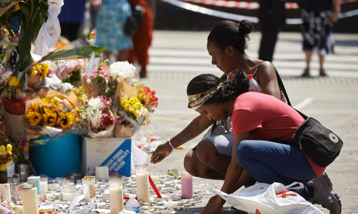 Well-wishers leave bunches of flowers as a tribute to the victims and the missing from the Grenfell Tower block fire close to the scene in North Kensington, west London, on June 19, 2017. (Niklas Halle'n/AFP/Getty Images)