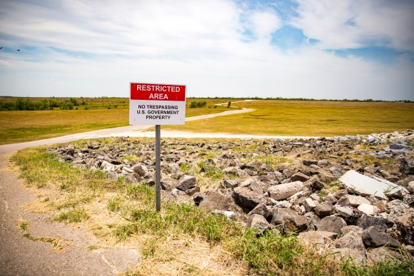 A sign next to a border patrol road that cuts through the levee behind Granjeno, Texas, warns that the area is restricted. (Benjamin Chasteen/The Epoch Times)