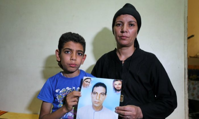Hanaa Youssef and Mina Habib, the widow and son of a man who was killed in a militant attack against Coptic Christians last month, hold the victim's portrait in Minya, Egypt June 8, 2017.  (Reuters/Mohamed Abd El Ghany)