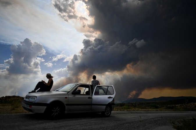 People watch the columns of smoke rising from a wildfire in Gois, Portugal, on June 20, 2017. (PATRICIA DE MELO MOREIRA/AFP/Getty Images)