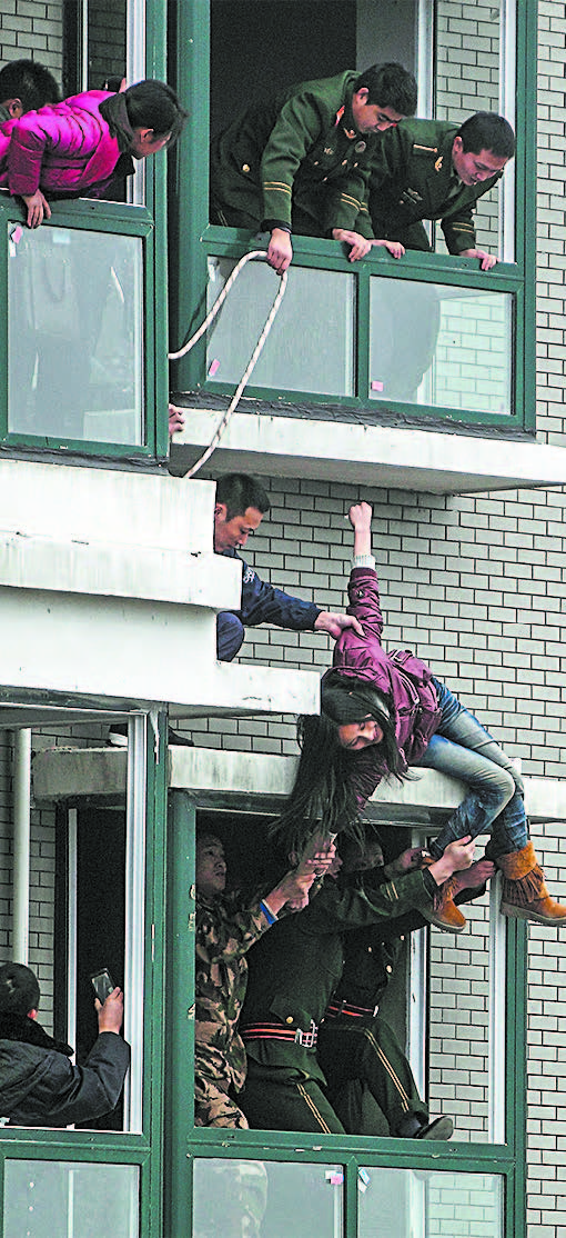 A Chinese woman who attempted to jump off the 33rd floor of an apartment building in Changsha, in China's Hunan Province, on Feb. 28, 2012. (STR/AFP/GETTY IMAGES)