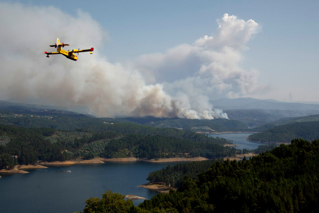 A firefighter plane works on a fire after a wildfire took dozens of lives on June 20, 2017 near Pedrogao Grande, in Leiria district, Portugal. (Pablo Blazquez Dominguez/Getty Images)