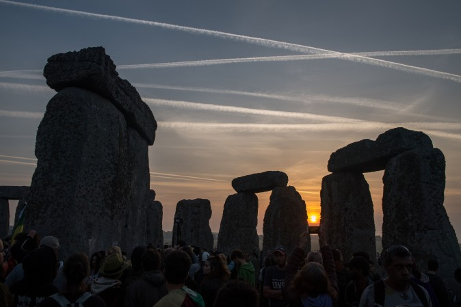 Revelers watch the sunrise as they celebrate the pagan festival of Summer Solstice at Stonehenge in Wiltshire, England, on June 21, 2017. The festival, which dates back thousands of years, celebrates the longest day of the year when the sun is at its maximum elevation. (CHRIS J RATCLIFFE/AFP/Getty Images)