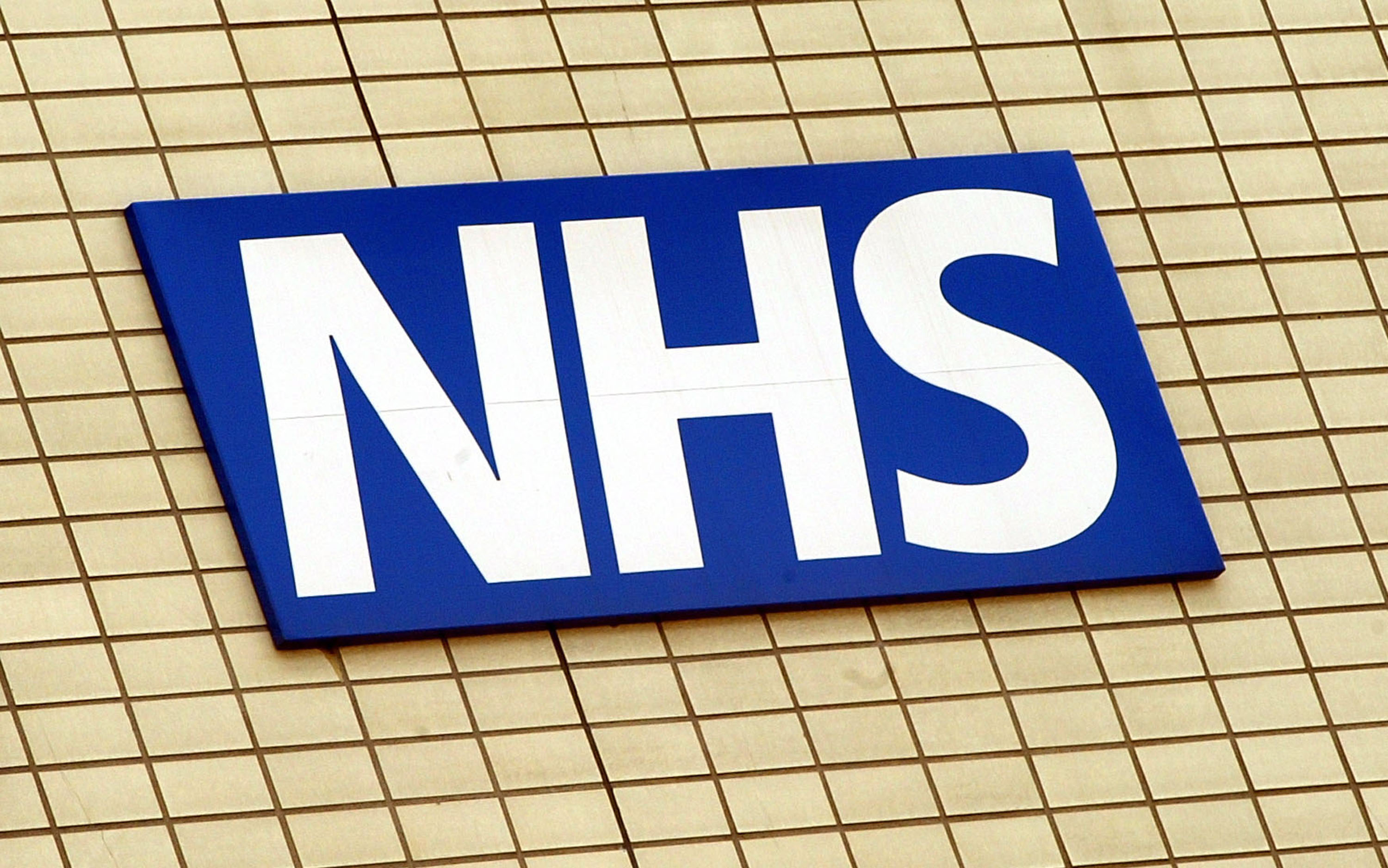 The National Health Service logo is shown on the wall outside St Thomas's Hospital in London, England May 7, 2003. (Scott Barbour/Getty Images)