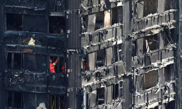 Members of the emergency services work inside burnt out remains of the Grenfell apartment tower in North Kensington, London, Britain on June 18, 2017. (Reuters/Neil Hall)