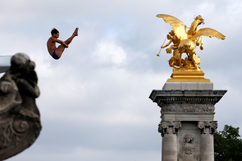 A diver performs from the Pont Alexandre III bridge into the River Seine in Paris, France, June 23, 2017 as Paris transforms into a giant Olympic park to celebrate International Olympic Days with a variety of sporting events for the public across the city during two days as the city bids to host the 2024 Olympic and Paralympic Games.  REUTERS/Jean-Paul Pelissier     TPX IMAGES OF THE DAY