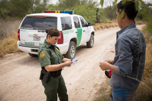 Marlene Castro, supervisory Border Patrol agent, checks the birth certificates of a group of unaccompanied minors who just crossed the Rio Grande from Mexico into the United States in Hidalgo County, Texas, on May 26. (Benjamin Chasteen/The Epoch Times)