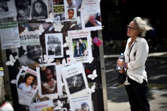 A woman looks at pictures of the victims of the fire at the Grenfell apartment tower stuck to a telephone box in North Kensington, London, Britain, June 23, 2017. (Reuters/Hannah McKay)