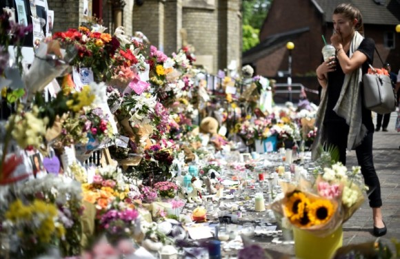 A woman looks at flowers, tributes and messages left for the victims of the fire at the Grenfell apartment tower in North Kensington, London, Britain, June 23, 2017. (Reuters/Hannah McKay)