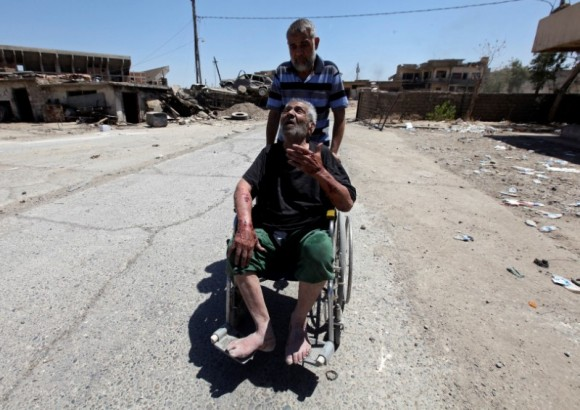 A displaced Iraqi man who fled from clashes pushes an old man in a wheelchair in the Old City of Mosul, Iraq June 24, 2017. (Reuters/Azad Lashkari)