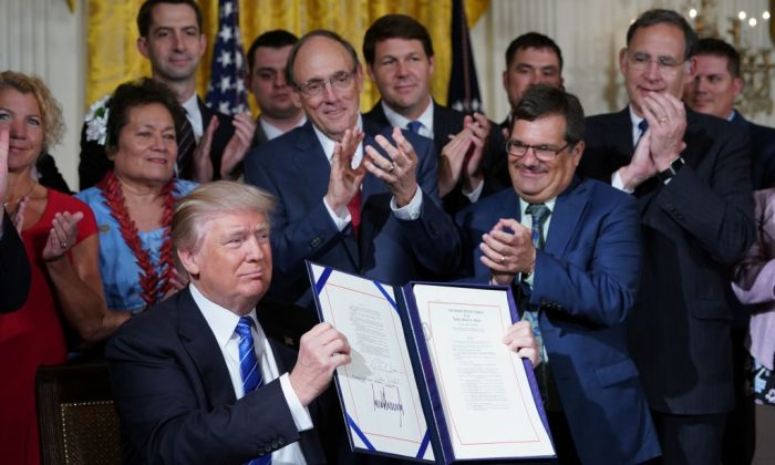 President Donald Trump holds up the bill after signing the Department of Veterans Affairs Accountability and Whistleblower Protection Act of 2017, in the East Room of the White House in Washington on June 23, 2017. (MANDEL NGAN/AFP/Getty Images)