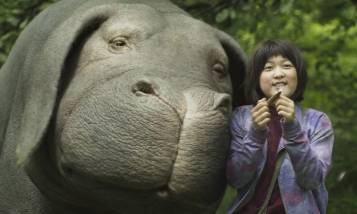 """This image released by Netflix shows Seo-Hyun Ahn as Mija and the character Okja in a scene from """"Okja."""" (Netflix via AP)"""