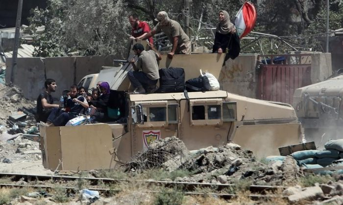 Iraqi security forces transport displaced civilians with an armoured fighting vehicle out of West Mosul during fighting with Islamic State militants in the Old City of Mosul, Iraq June 24, 2017. (Reuters/Marius Bosch)