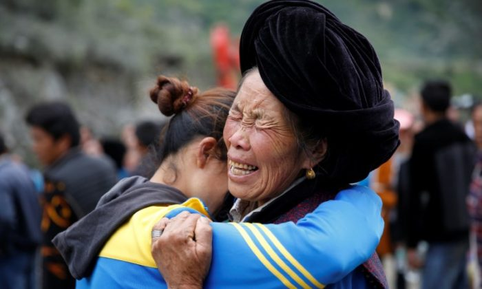 Relatives of victims react at the site of a landslide in the village of Xinmo, Mao County, Sichuan Province, China June 26, 2017. (Reuters/Aly Song)