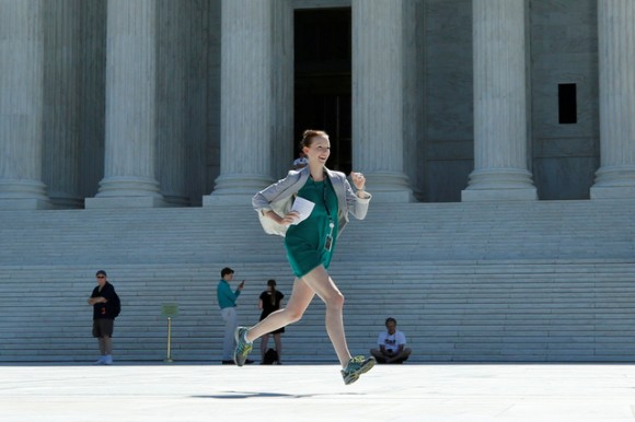 A news assistant runs out after the U.S. Supreme Court granted parts of the Trump administration's emergency request to put his travel ban into effect immediately while the legal battle continues, in Washington, U.S., June 26, 2017. REUTERS/Yuri Gripas