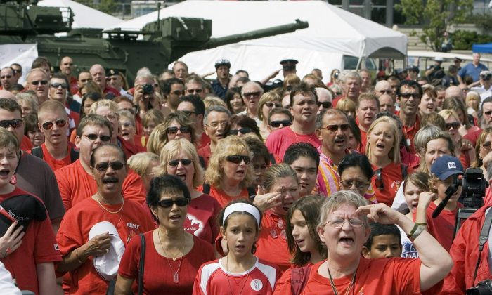 FILE-- Supporters sing 'O Canada' during a support the troops rally in Toronto in this August 24, 2007 photo. A new study says more than half of Canadian high school choir students surveyed are out of tune when it comes to the national anthem. THE CANADIAN PRESS/Frank Gunn