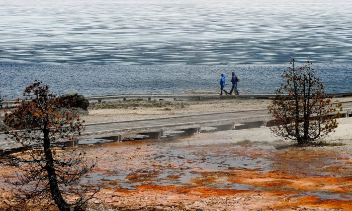 Tourists walk beside Yellowstone Lake at the West Thumb Geyser Basin in the Yellowstone National Park, Wyoming on June 2, 2011. (Mark Ralston/AFP/Getty Images)